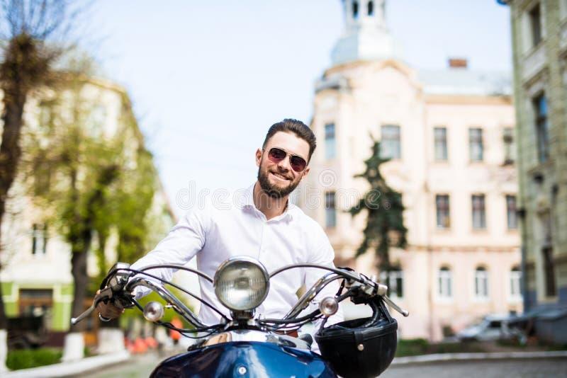 Giovane motorino bello di guida dell'uomo d'affari attraverso la città della via fotografie stock libere da diritti