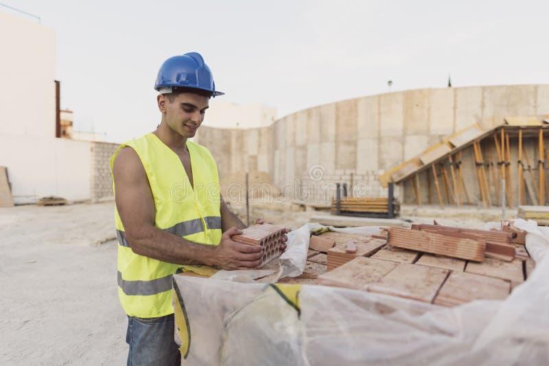 Giovane muratore con il mattone nella casa industriale co del sito fotografia stock