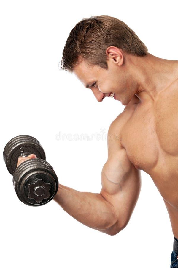 Giovane muscolare che alza un dumbbell immagine stock libera da diritti