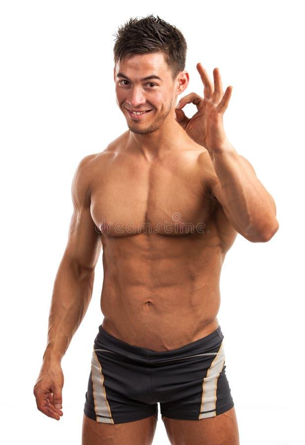 Giovane muscolare che mostra il segno giusto immagine stock libera da diritti