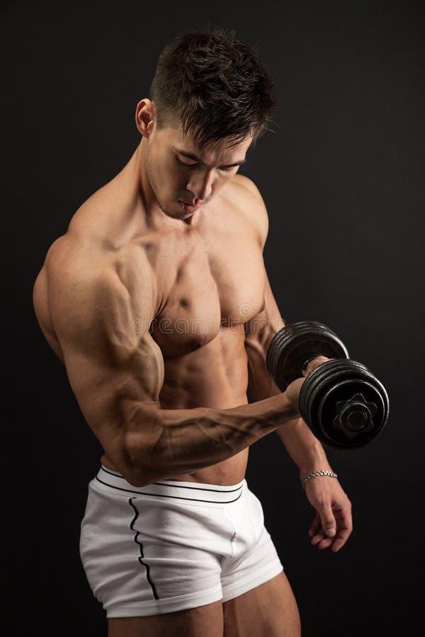Giovane muscolare che solleva una testa di legno fotografia stock