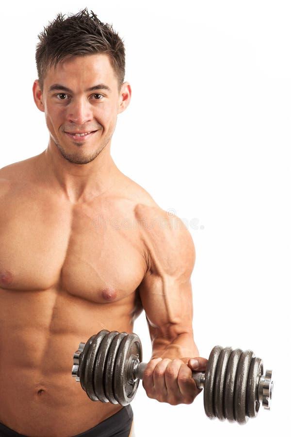 Giovane muscolare che solleva una testa di legno sopra bianco immagine stock