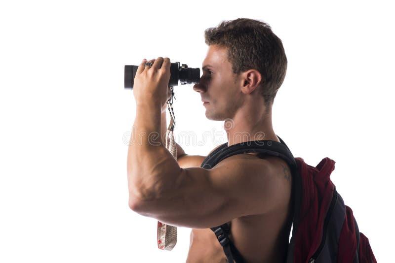 Giovane muscolare senza camicia con binoculare e lo zaino fotografia stock libera da diritti