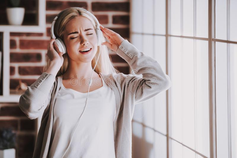 Giovane musica d'ascolto sorridente della donna in cuffie immagini stock libere da diritti