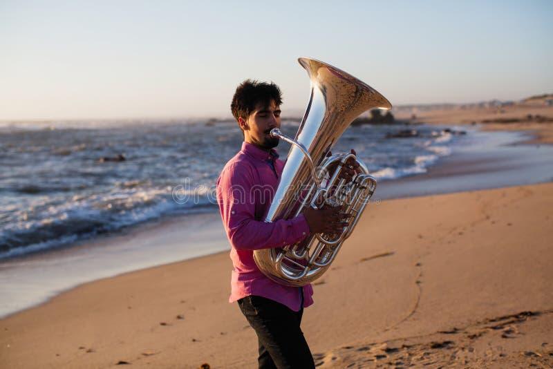 Giovane musicista che gioca la tuba sull'hobby della costa di mare fotografie stock