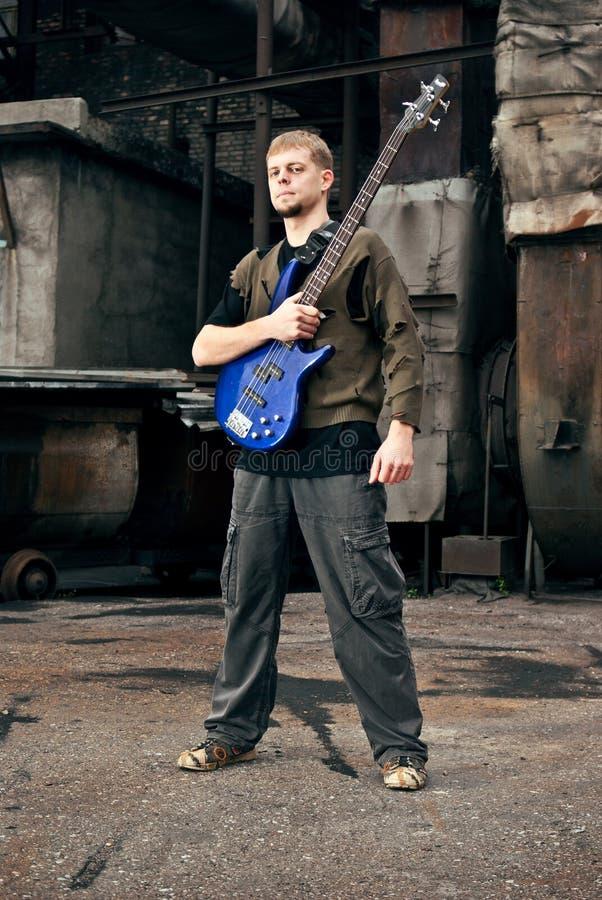 Giovane musicista con la chitarra nello stile industriale fotografia stock