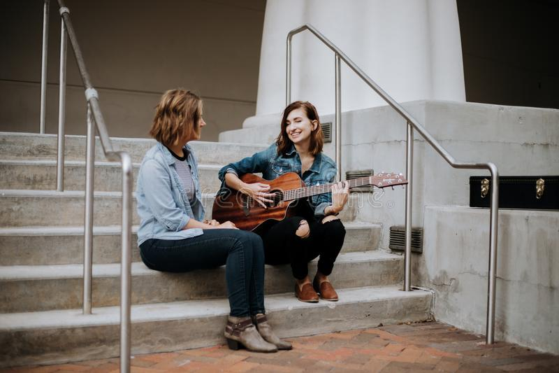 Giovane musicista femminile sveglio Friends Modeling Outside sui provvedimenti concreti fotografie stock libere da diritti