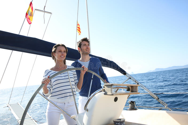Giovane navigazione delle coppie sulla barca fotografie stock libere da diritti