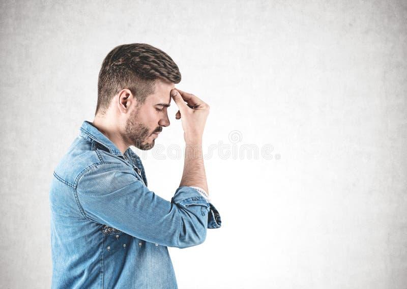 Giovane nel pensiero della camicia dei jeans duro, concreto fotografie stock