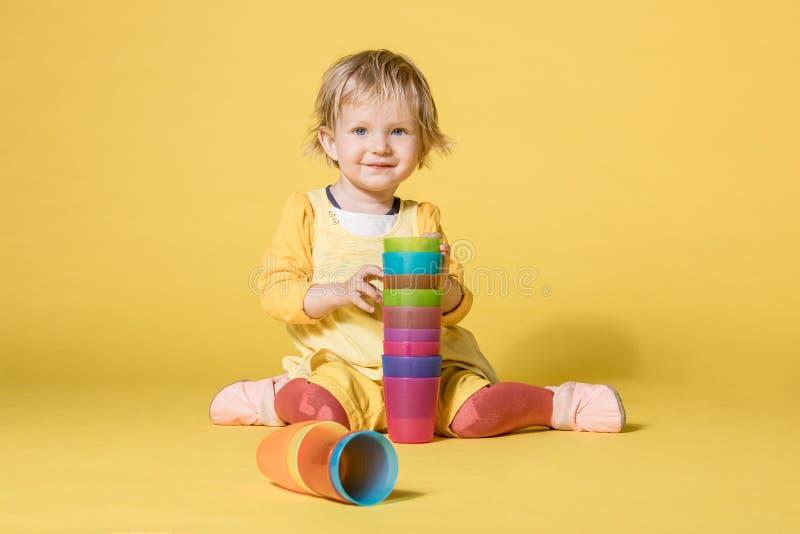 Giovane neonata in vestito giallo su fondo giallo immagine stock