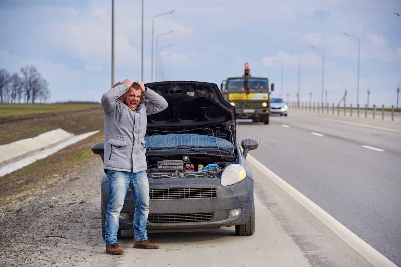 Giovane nervoso vicino all'automobile rotta sulla strada principale fotografie stock libere da diritti