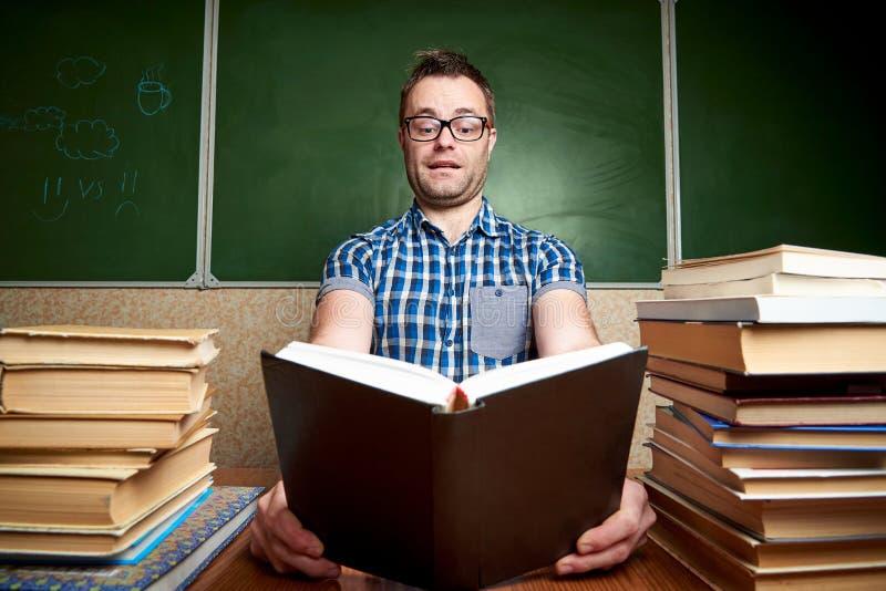 Giovane non rasato scompigliato in vetri che legge un libro alla tavola con i mucchi dei libri fotografia stock