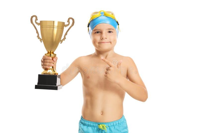 Giovane nuotatore del ragazzo con indicare dorato del trofeo fotografia stock