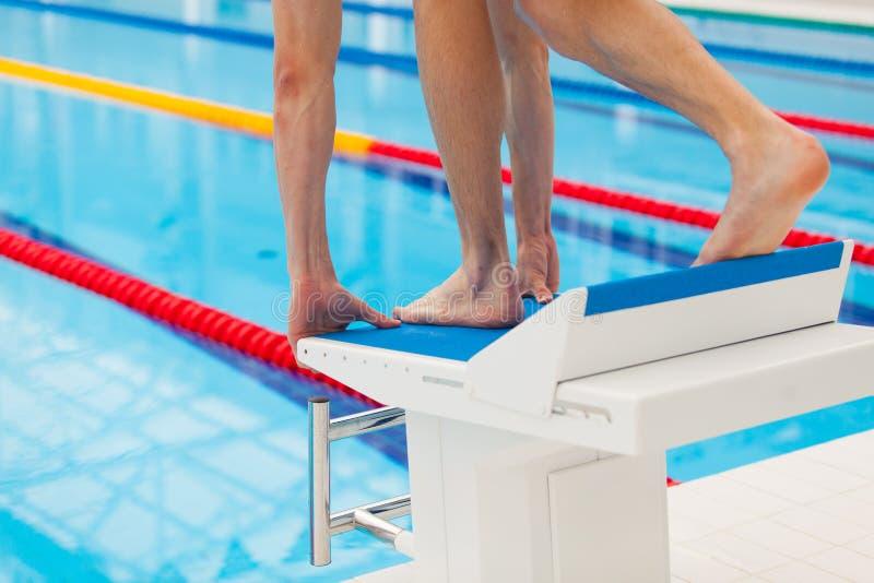Giovane nuotatore muscolare nella posizione bassa sul blocchetto iniziare in una piscina fotografie stock libere da diritti