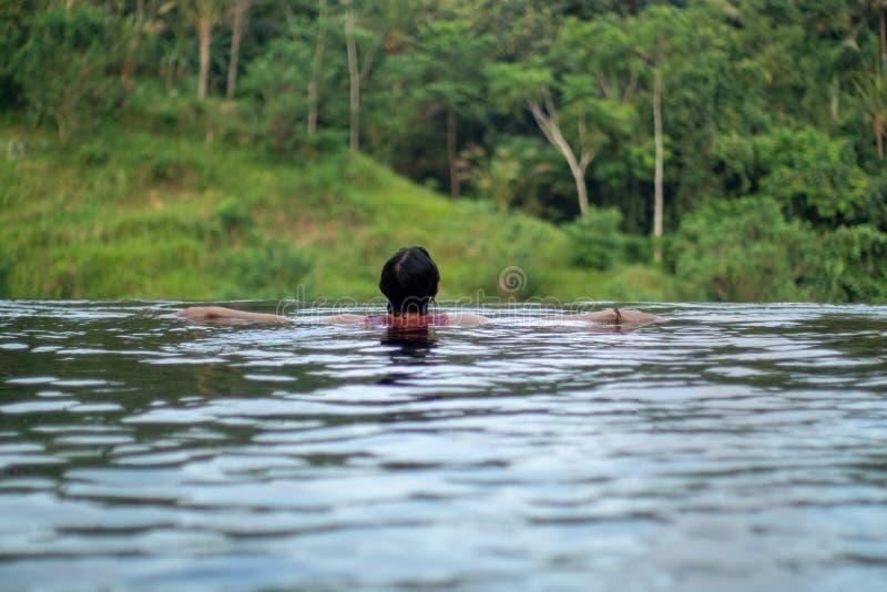 Giovane nuoto asiatico della ragazza nello stagno di infinito con la bella vista ? presa le foto dalla parte posteriore fotografia stock