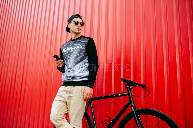 Giovane in occhiali da sole che tengono un aggeggio, stante vicino alla bicicletta fotografia stock libera da diritti