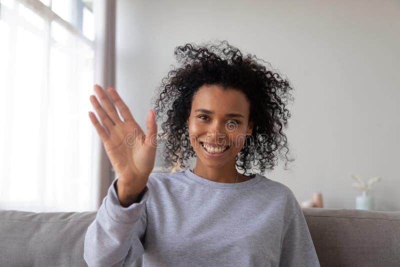 Giovane ondeggiamento femminile nero sorridente avendo video chiamata immagine stock libera da diritti