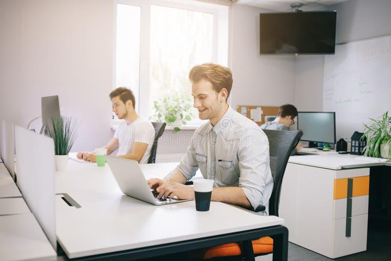 Giovane operaio che si siede in un ufficio al computer Free lance in una camicia bianca Il progettista si siede davanti alla fine immagini stock libere da diritti