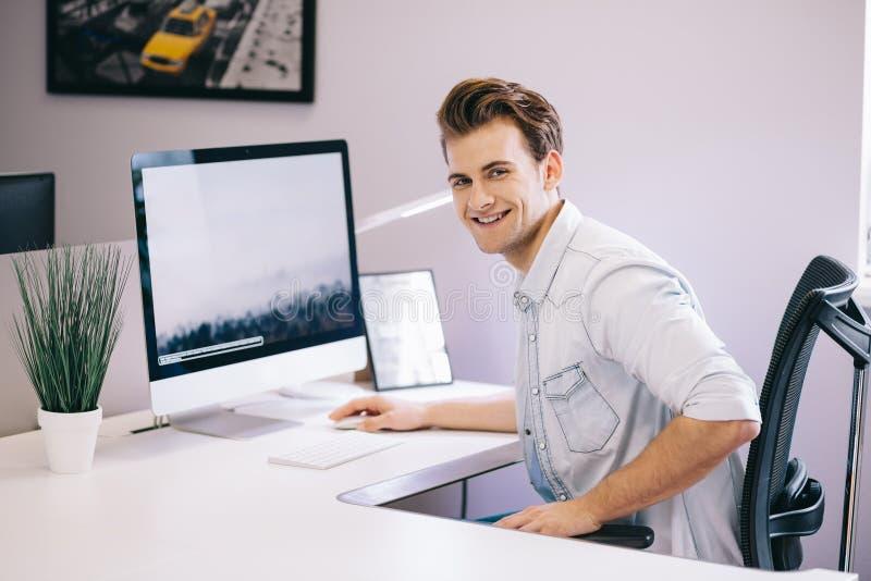 Giovane operaio che si siede in un ufficio al computer Free lance in una camicia bianca Il progettista si siede davanti alla fine fotografie stock