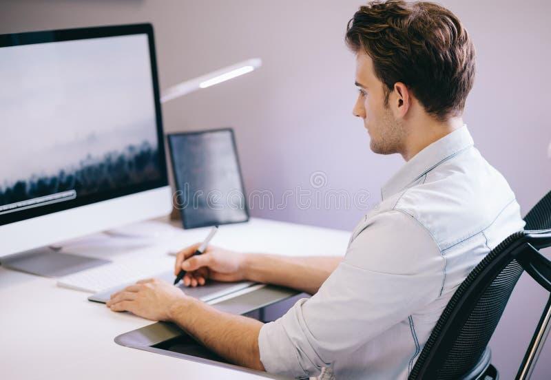 Giovane operaio che si siede in un ufficio al computer Free lance in una camicia blu Il progettista si siede davanti alla finestr fotografia stock