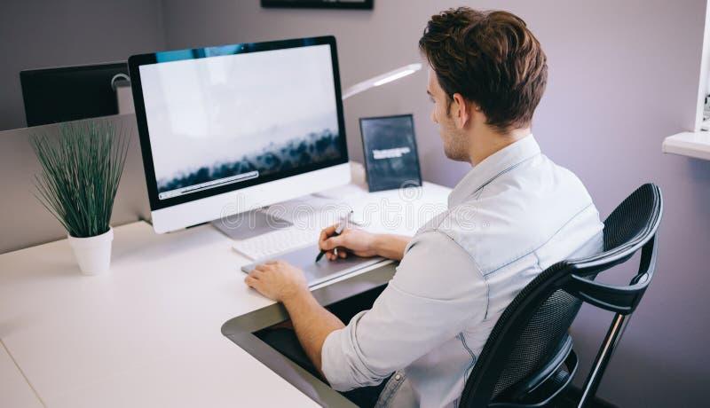 Giovane operaio che si siede in un ufficio al computer Free lance in una camicia blu Il progettista si siede davanti alla finestr fotografie stock