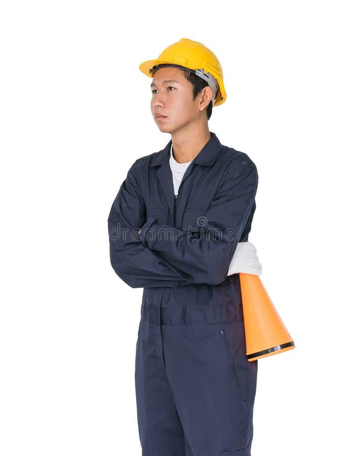 Giovane operaio con il casco giallo che tiene un megafono fotografia stock