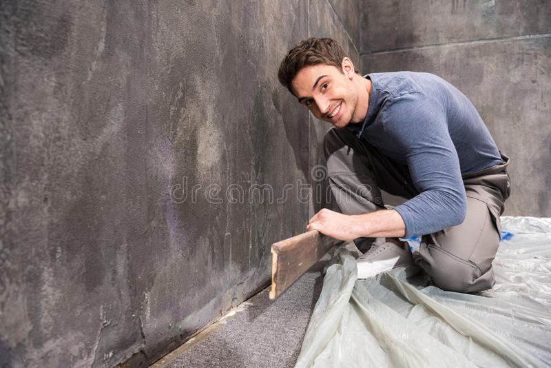 Giovane operaio professionista sorridente che ripara pavimento immagine stock libera da diritti