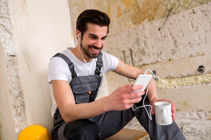 Giovane operaio sorridente che gode del suo tempo della rottura immagini stock libere da diritti