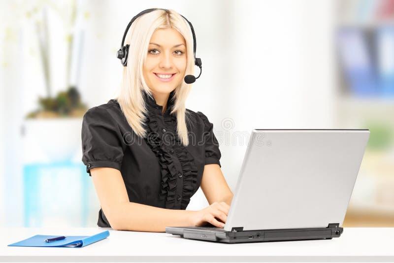 Giovane operatore femminile di servizio di assistenza al cliente che lavora al computer portatile immagine stock libera da diritti
