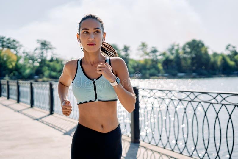 Giovane operatrice di fitness che corre sul fiume fotografia stock
