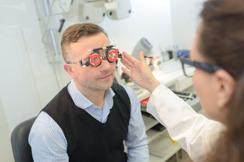 Giovane optometrista femminile felice che fa prova di visione per il paziente maschio fotografia stock libera da diritti