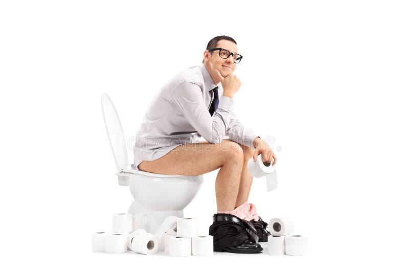 Giovane pacifico che si siede su una toilette immagini stock