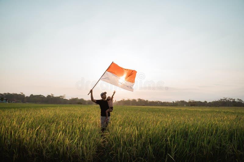 Giovane padre asiatico con doughter che agita bandiera indonesiana fotografia stock libera da diritti