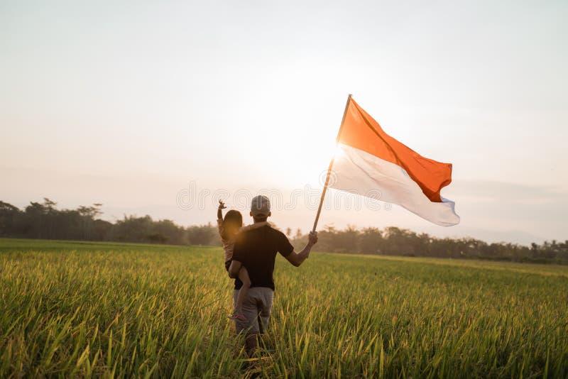 Giovane padre asiatico con doughter che agita bandiera indonesiana immagini stock libere da diritti