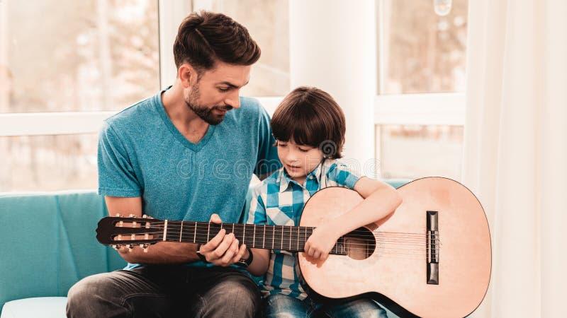 Giovane padre barbuto Playing sulla chitarra con il figlio immagini stock libere da diritti