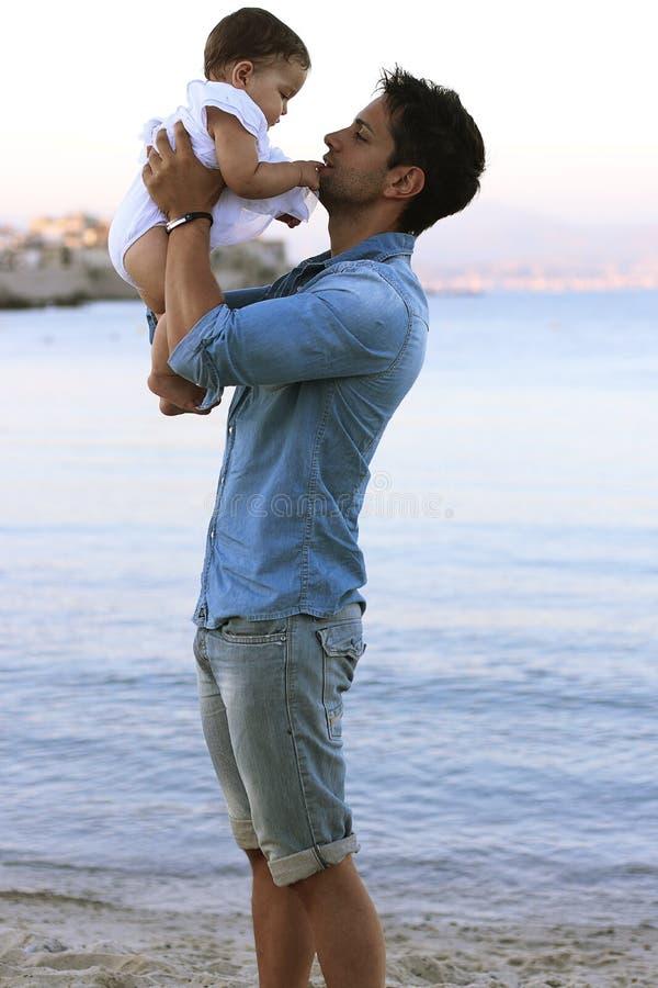 Giovane padre bello che tiene la sua neonata sulla spiaggia immagine stock libera da diritti