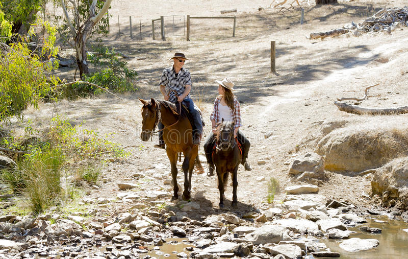 Giovane padre come istruttore del cavallo di giovane figlia teenager che guida il cappello d'uso del cowgirl del piccolo cavallin fotografie stock