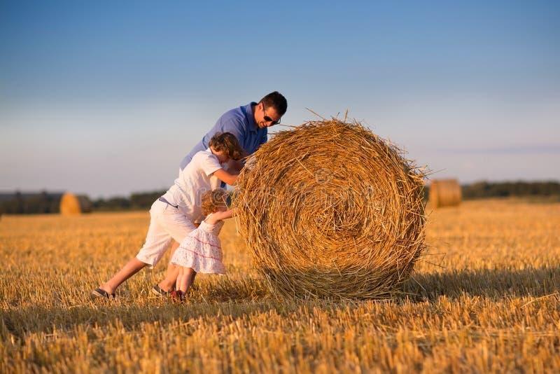 Giovane padre e childrem due che giocano nel campo al tramonto fotografie stock libere da diritti