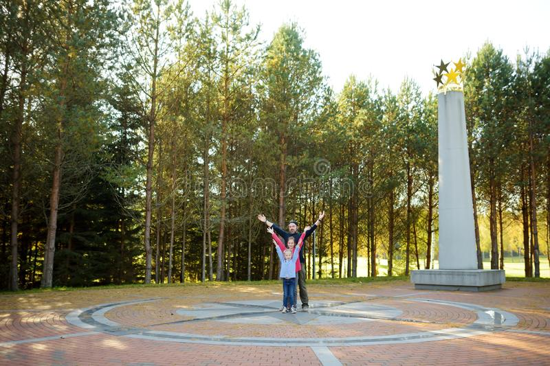 Giovane padre e due bambini divertendosi al centro geografico di Europa, situato in Lituania immagine stock