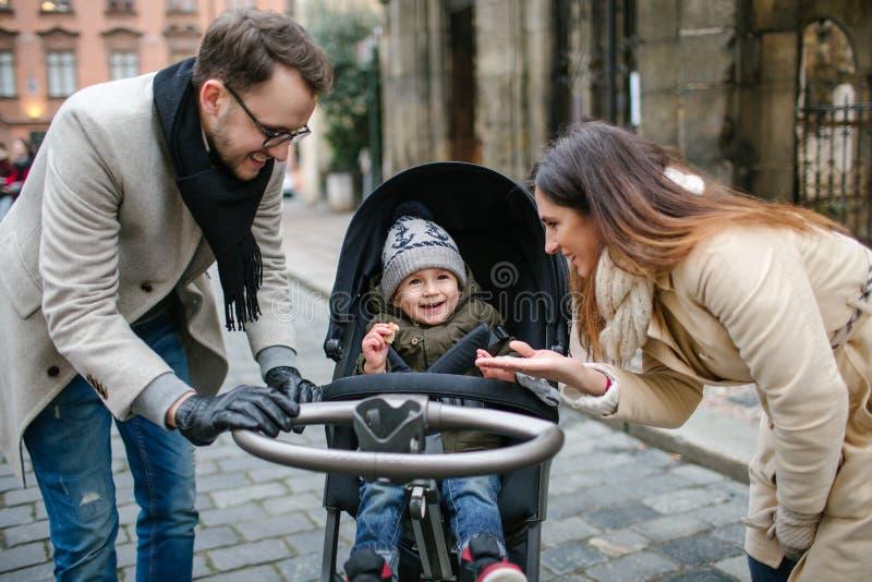 Giovane padre e madre con il figlio in passeggiatore di bambino all'aperto immagine stock libera da diritti