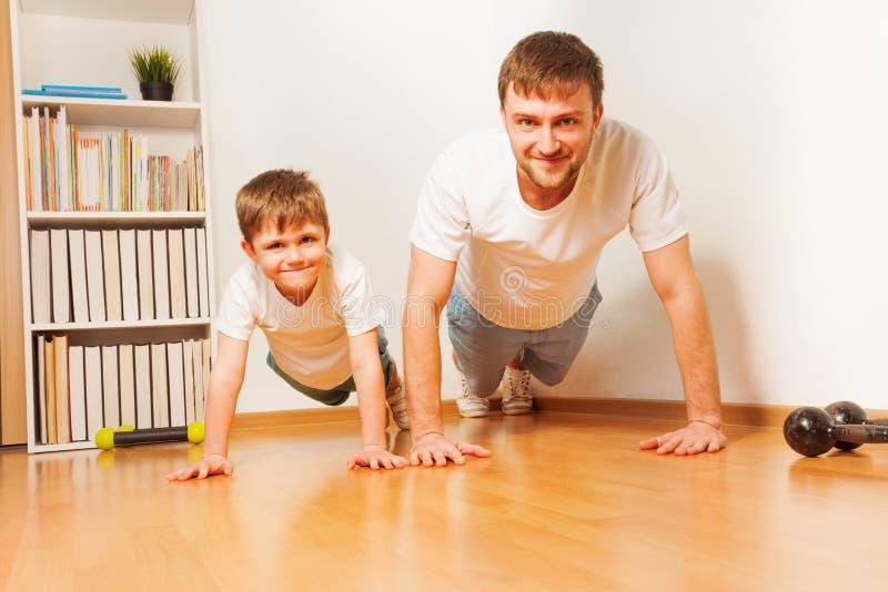 Giovane padre e suo il figlio che spingono verso l'alto alla stanza fotografie stock