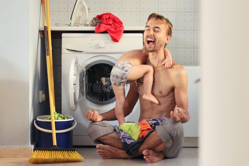 Giovane padre esaurito del marito che si siede nella posa del loto vicino alla lavatrice con il mucchio dei vestiti e del bambino fotografia stock