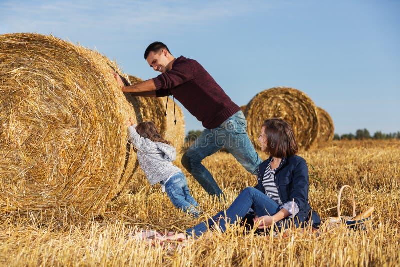 Giovane padre felice e sua la ragazza di due anni che spingono una balla di fieno fotografie stock