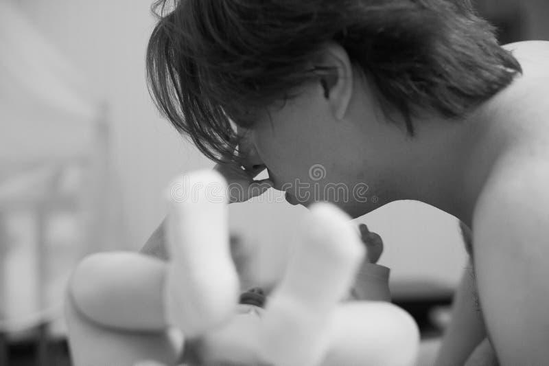 Giovane padre imbrogliato con il suo piccolo bambino Il papà gioca con sua figlia e mostra lei la lingua Tonning in bianco e nero fotografie stock
