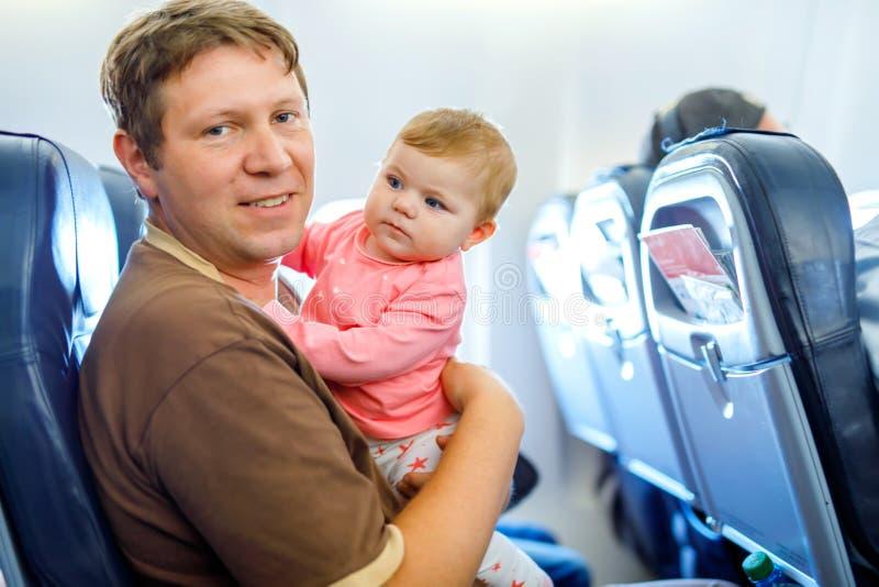 Giovane padre stanco e sua figlia gridante del bambino durante il volo sull'aeroplano che va sulle vacanze fotografie stock libere da diritti