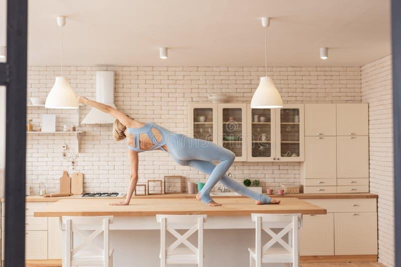 Giovane padrone esagerato di yoga in attrezzatura professionale blu-chiaro immagini stock libere da diritti