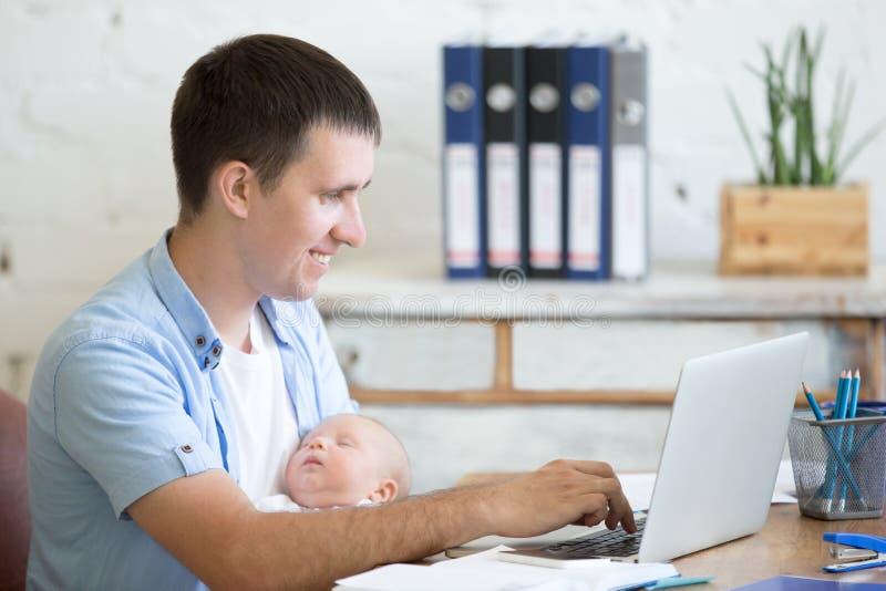 Giovane papà che lavora con il suo bambino nell'ufficio immagine stock