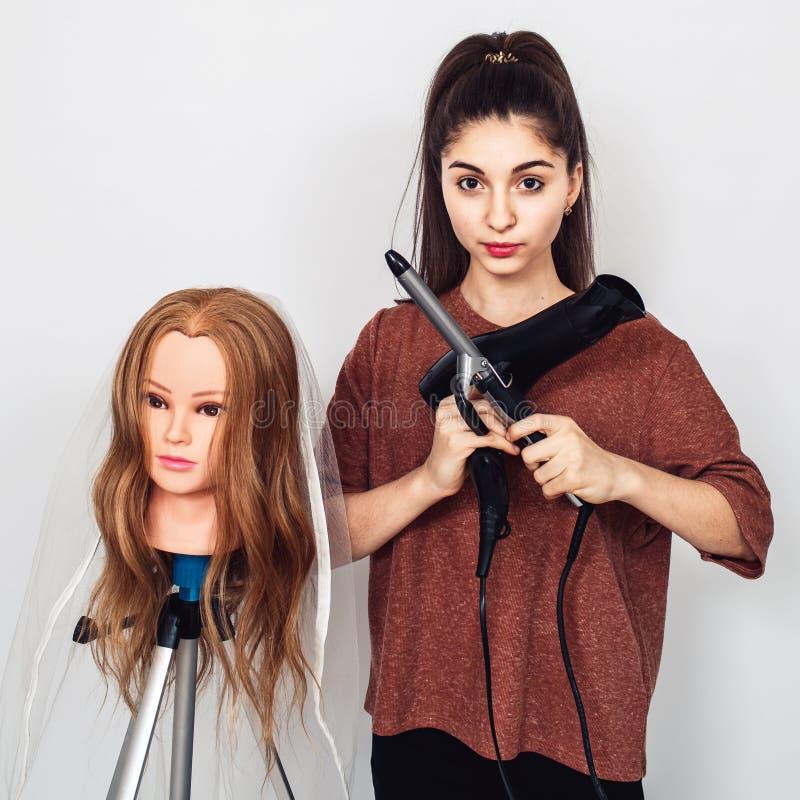 Giovane parrucchiere con un ferro di arricciatura, il fon e una testa del manichino su un treppiede fotografia stock