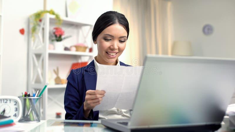 Giovane parte anteriore di seduta leggente femminile sorridente della lettera del computer portatile, corrispondenza fotografie stock libere da diritti
