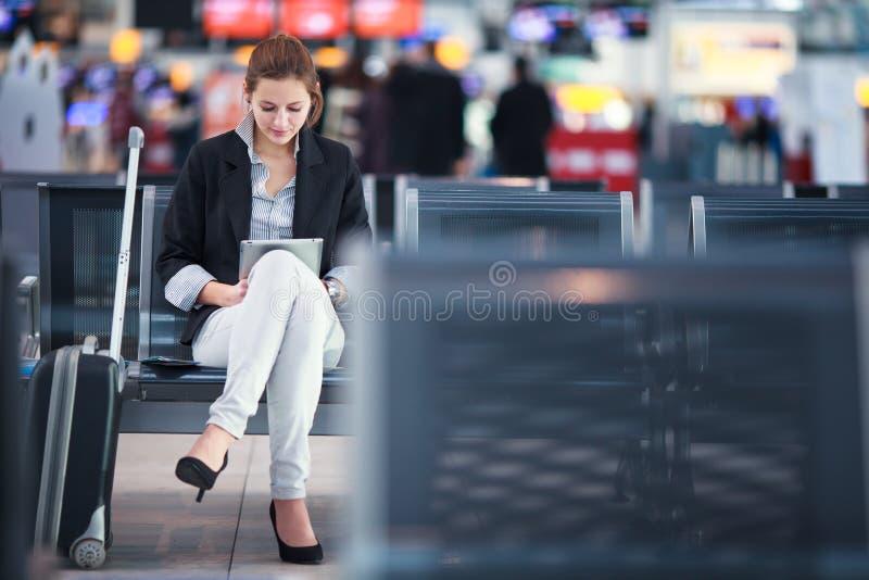 Giovane passeggero femminile all'aeroporto, facendo uso del suo computer della compressa fotografia stock libera da diritti